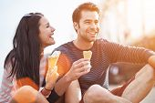 stock photo of flirt  - romantic couple eating ice cream at park - JPG