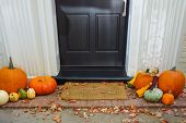 Pumpkins on front steps of home during  Halloween/Thanksgiving season