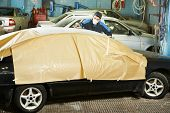 professional repairman worker in automotive industry sanding roof of body car