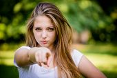 stock photo of cheeky  - Cheeky teen girl showing to the front with finger  - JPG