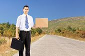 Young businessman holding a leather suitcase and hitchhiking on an open road