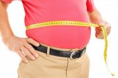 stock photo of obese man  - Fat mature man measuring his belly with measurement tape - JPG