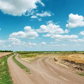 two dirty roads under blue cloudy sky