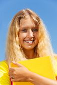 stock photo of 13 year old  - Close portrait of happy blond 13 years old girl stand with with the yellow book in the park on bright sunny summer day - JPG
