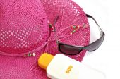 Pink Beach Hat, Bottle Of Balm Solar And Glasses On White.