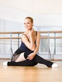 Ballet dancer does exercises sitting on the wooden floor in the classroom with barre and mirrors