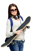 Half-length portrait of teenager with skateboard wearing sunglasses, headphones and knapsack, isolated on white. Concept of young generation