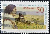 A stamp printed in USA shows image celebrating the first Americans coming over from Asia