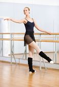 stock photo of ballet barre  - Wearing leotard and warmers ballet dancer dances near barre and mirrors in studio - JPG