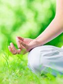 Close up of female hand zen gesturing. Woman sits in asana position. Concept of healthy lifestyle and relaxation