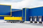 picture of front-entry  - warehouse painted yellow and blue with a trailer in front - JPG