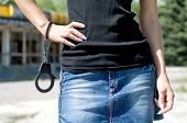 Woman in mini skirt holding handcuffs.