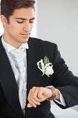 Handsome bridegroom watching the clock wearing a suit