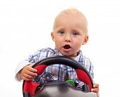 Little boy holding a toy steering wheel over white