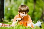 Image of cute boy playing in park with magnifier