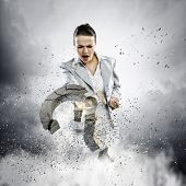 Image of businesswoman destroying with arm stone question mark