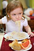 Little girl with pigtails eating spaghetti with a spoon in a cafe