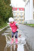 Happy little girl in a pink vest and rubber boots jumps into a puddle