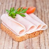 bread with sliced ham, fresh tomatoes and parsley closeup on rustic wooden background