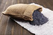 stock photo of opiate  - Poppy seeds in sack on table close - JPG