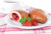 Fresh baked pasties with strawberries on plate on table close-up