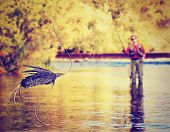 stock photo of fly rod  - a person fly fishing with a big fly in front done with a soft vintage instagram like filter - JPG