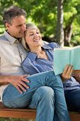 Affectionate couple reading book on bench in a park