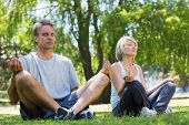 Full length of couple sitting in lotus position in the park