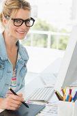 Blonde happy designer using digitizer at her desk in creative office