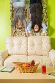 Two women stand upside down and hold on to the sofa