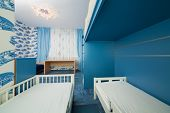 Beautiful modern children bedroom with wallpapers with cars.