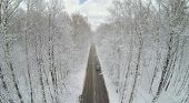 Road with car in big winter forest with frosted trees. Aerial view