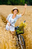 Girl rides bicycle and waves hand in rye field. Concept of rural lifestyle and sport