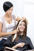 Hair stylist tries lock of dyed blond hair on the client sitting on the chair in the hairdress salon