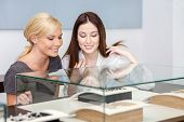 Two girls looking at glass case with jewelry at jeweler's shop. Concept of wealth and luxurious life