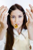 Woman holding necklace with yellow sapphire at jeweler's shop. Concept of wealth and luxurious life
