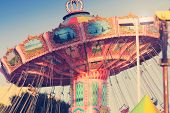 stock photo of carnival ride  - Nostalgic street fair ride in subtle vintage tones - JPG