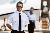 Portrait of confident pilot standing with stewardess and private jet in background at terminal