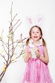 Cheerful little girl decorating magnolia tree branch with Easter eggs