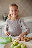 pic of 7-year-old  - Portrait of a 7 years old girl cutting vegetables in kitchen at home - JPG