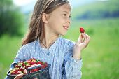 Child eating strawberries in a spring floral field