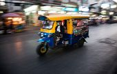 BANGKOK - JAN 24: A tuk tuk taxi transports passengers  on Jan 24, 2014 in Bangkok, Thailand. Tuk tuks can be hired from as little as $1 or B30 a fare for shop trips.