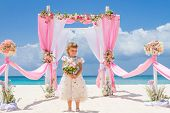 pic of wedding arch  - young happy kid girl in beautiful dress on tropical wedding setup background - JPG