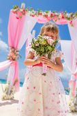 young happy kid girl in beautiful dress on tropical wedding setup background