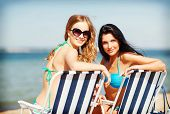 summer holidays and vacation - girls sunbathing on the beach chairs