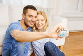 love, family, technology and happiness concept - smiling couple taking self portrait picture with di