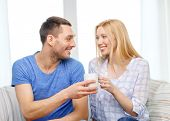 love, family, healthy food and happiness concept - smiling man giving cup of tea or coffee to wife o