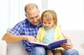 family, children, education, school and happy people concept - smiling father and daughter with book at home