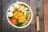 Spicy curry instant noodles soup with fork on wooden dining table. Fresh hot with steamed smoke.