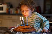 Adorable Four Year Old Boy Celebrating His Birthday And Blowing Off The Candles On The Cake, Indoor